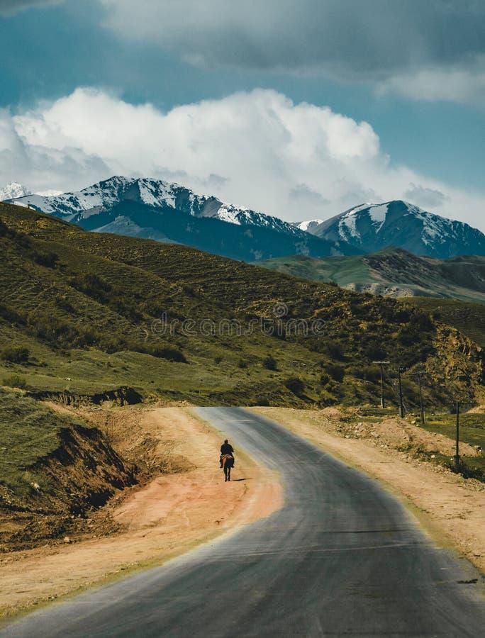 Homem na equitação na rua no estepe com as montanhas de Tian Shan no fundo, central Ásia de Cazaquistão fotos de stock royalty free
