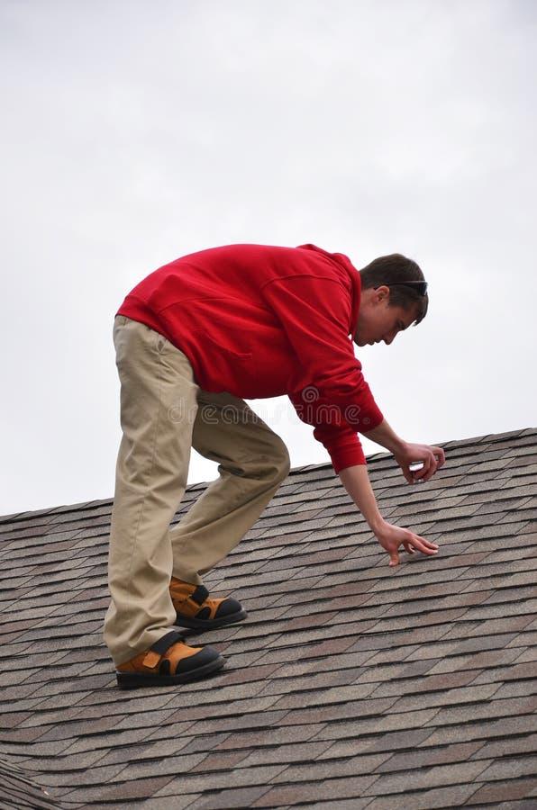 Homem na escada em um telhado fotografia de stock