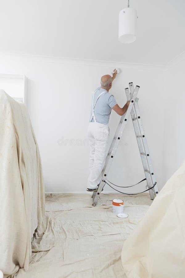 Homem na escada que decora a sala doméstica com escova de pintura foto de stock