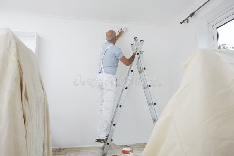 Homem na escada que decora a sala doméstica com escova de pintura fotografia de stock