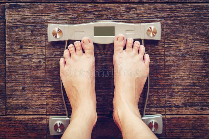 Homem na escala do peso no fundo de madeira do assoalho, conceito da dieta imagens de stock royalty free