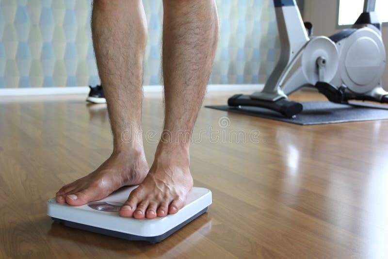 Homem na escala do peso para o peso da verificação, conceito da dieta foto de stock royalty free