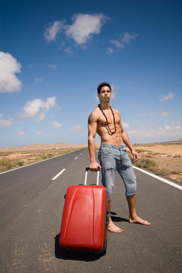 Homem na estrada com sua mala de viagem foto de stock