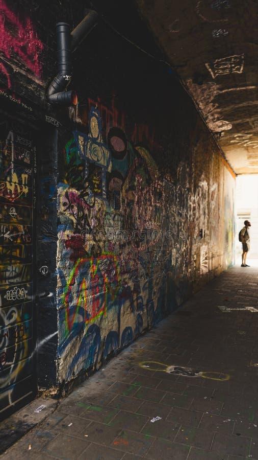 Homem na extremidade da aleia, admirando a arte dos grafittis, rua dos grafittis imagens de stock