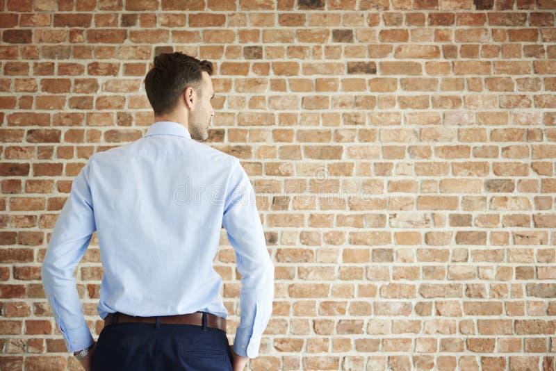 Homem na frente da parede de tijolo imagens de stock