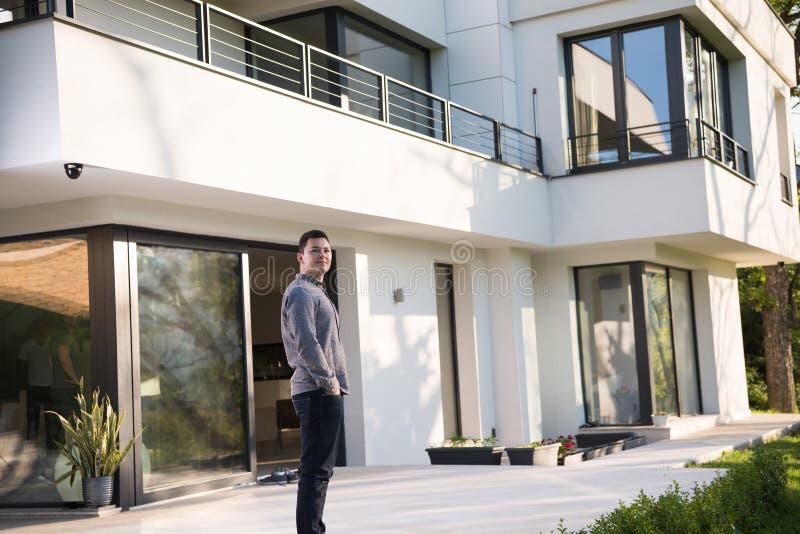 Homem na frente de sua casa de campo home luxuosa imagens de stock royalty free