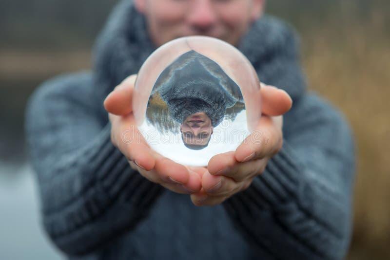 Homem na frente do lago que guarda uma bola de vidro imagens de stock