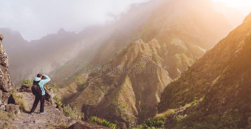 Homem na imagem de fatura rochosa da alta altitude da paisagem da montanha na frente de uma ravina profunda A luz morna do sol en fotos de stock