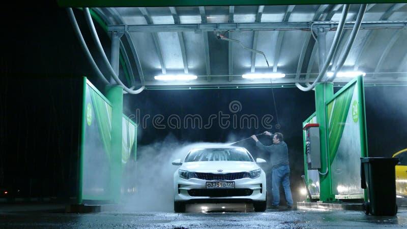 Homem na lavagem de carros manual na noite imagens de stock