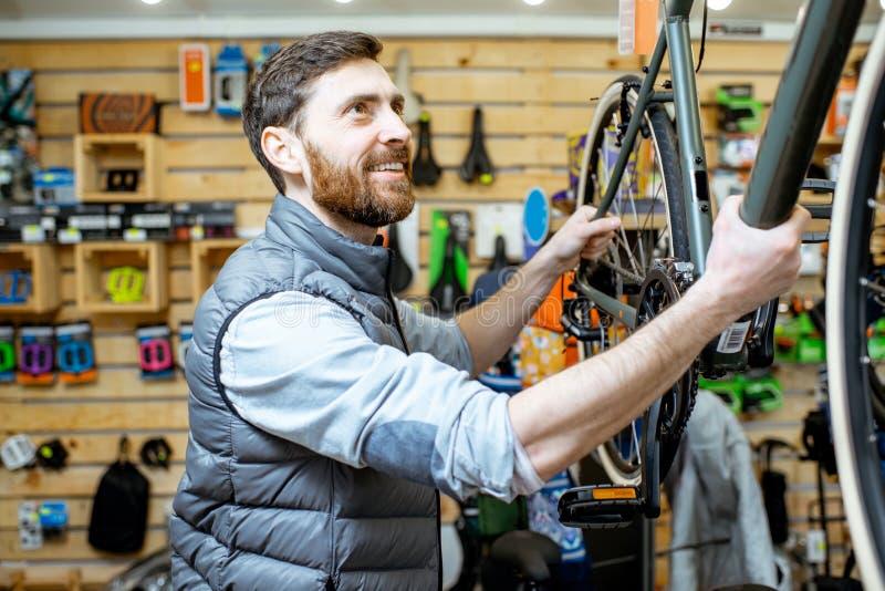 Homem na loja da bicicleta imagens de stock