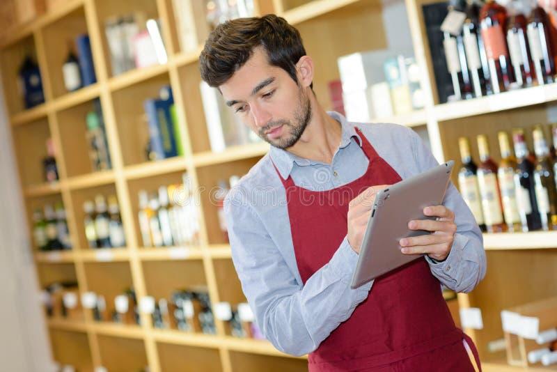 Homem na loja de bebidas que guarda o tablet pc foto de stock