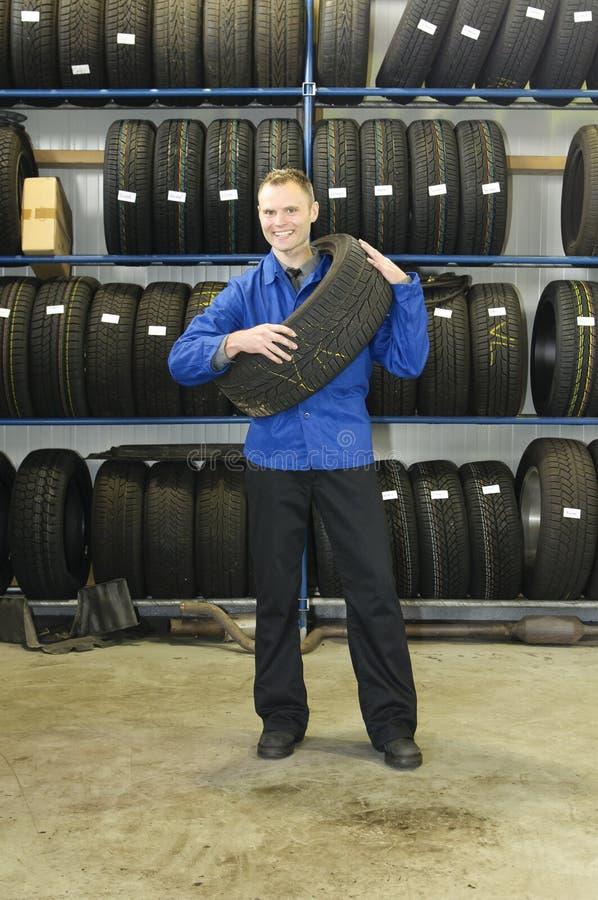 Homem na loja do pneu com um pneu, fotografia de stock royalty free