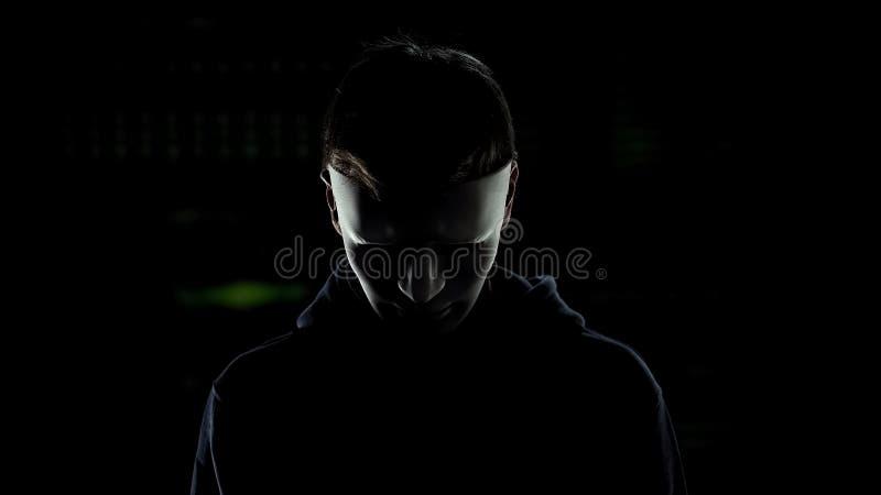Homem na máscara assustador isolada no fundo escuro, identidade escondendo do assassino em série imagens de stock