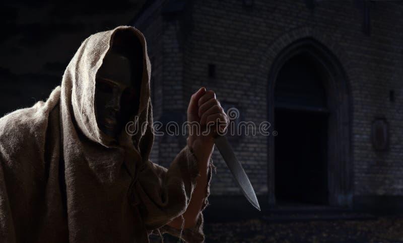Homem na máscara do ferro com faca imagem de stock royalty free