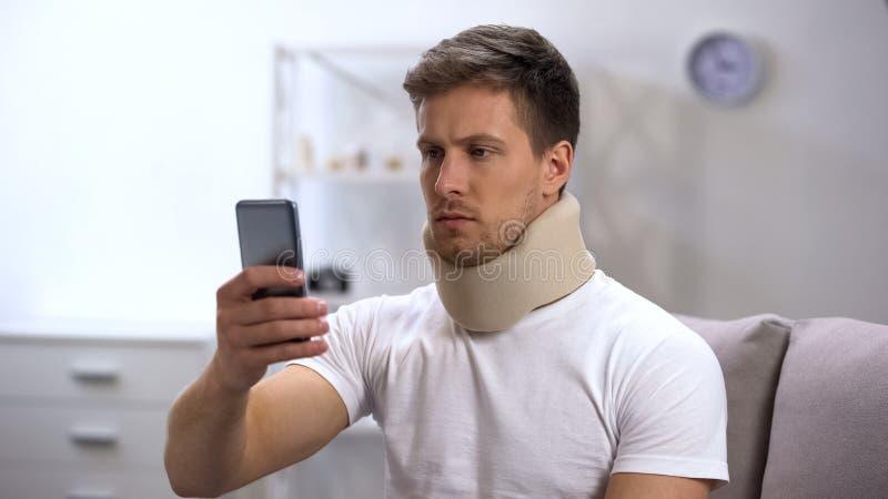 Homem na mensagem cervical no telefone celular, dor de sentimento da leitura do colar da espuma no pescoço fotografia de stock