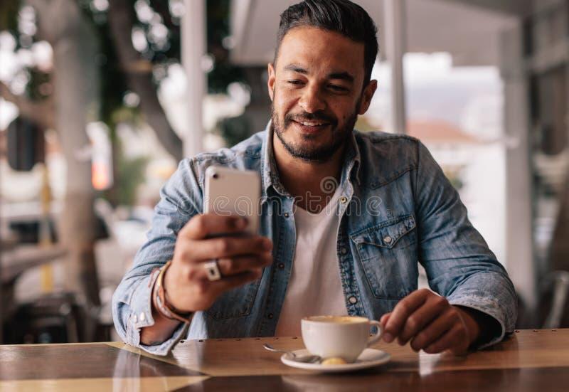 Homem na mensagem de texto da leitura da cafetaria no telefone celular imagem de stock royalty free
