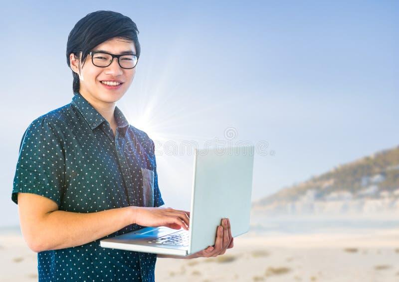 Homem na moda com o portátil contra a praia obscura foto de stock royalty free