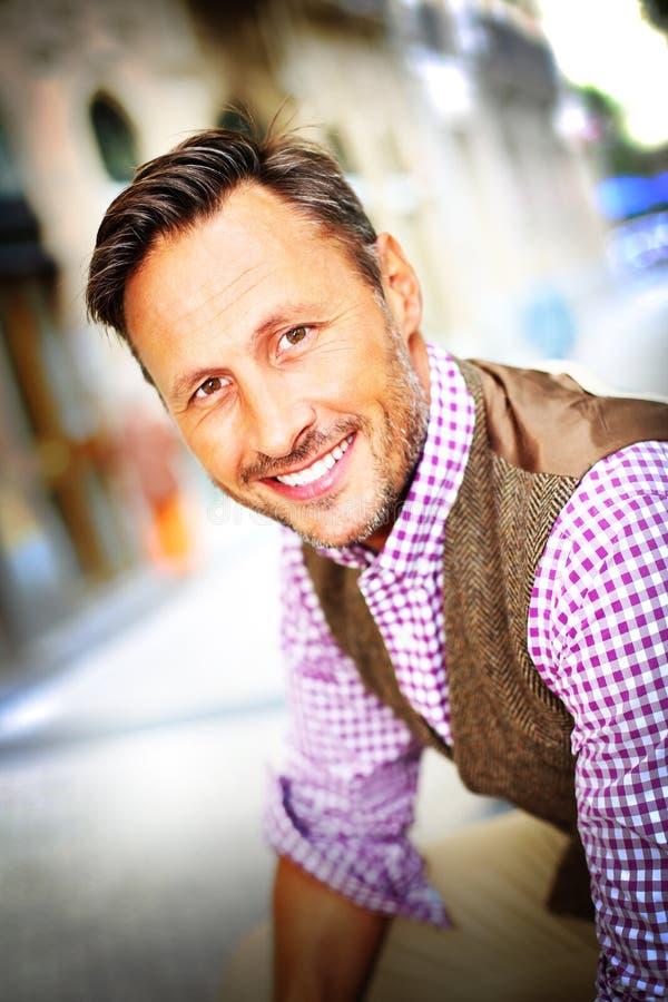 Homem na moda de sorriso que está na cidade imagem de stock royalty free