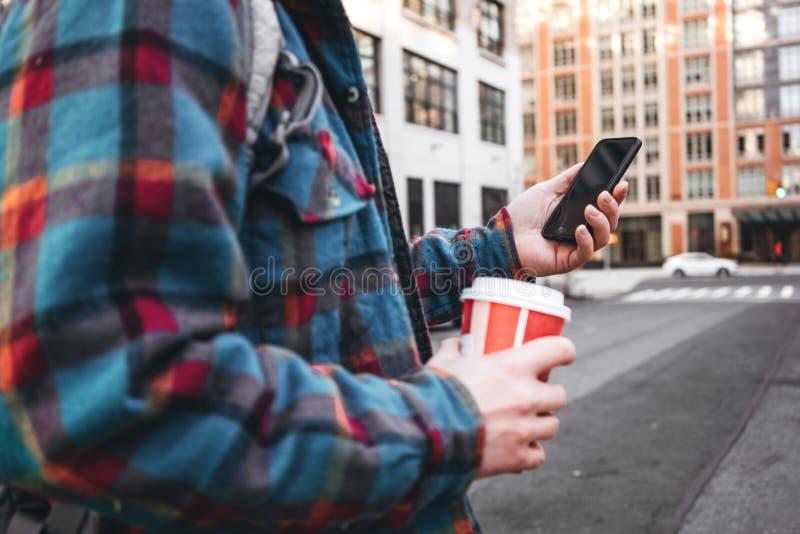 Homem na moda que anda através da rua grande da cidade com o copo do café quente e que usa o smartphone para a relação video com  imagem de stock