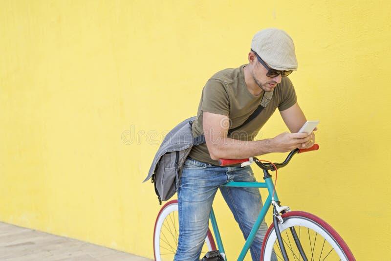 Homem na moda que usa seu smartphone fora foto de stock royalty free