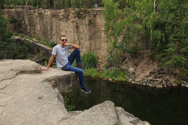Homem na montanha rochosa perto do lago imagem de stock