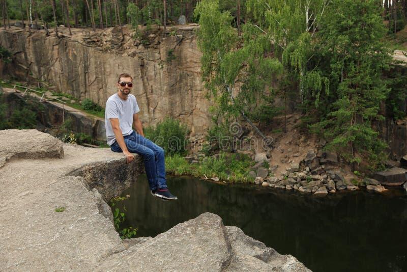 Homem na montanha rochosa perto do lago foto de stock royalty free