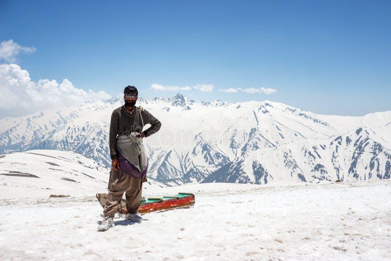 Homem na neve com pequeno trenó fotografia de stock