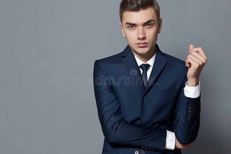 Homem na obscuridade - camisa branca e laço do terno azul que levantam o estúdio fotos de stock
