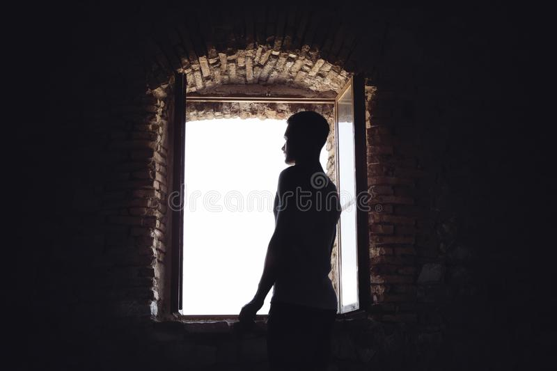 Homem na obscuridade iluminada pelo sol de uma janela imagens de stock royalty free