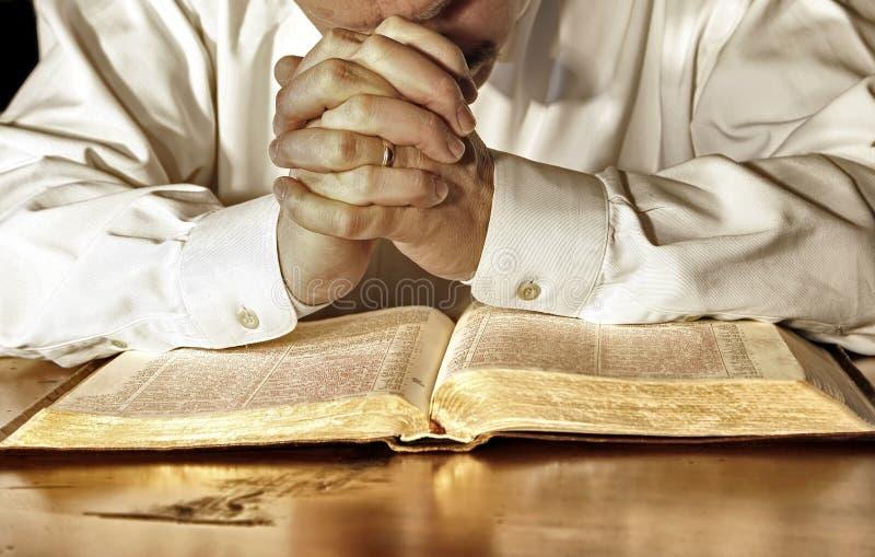 Homem na oração profunda sobre sua Bíblia Sagrada fotos de stock royalty free