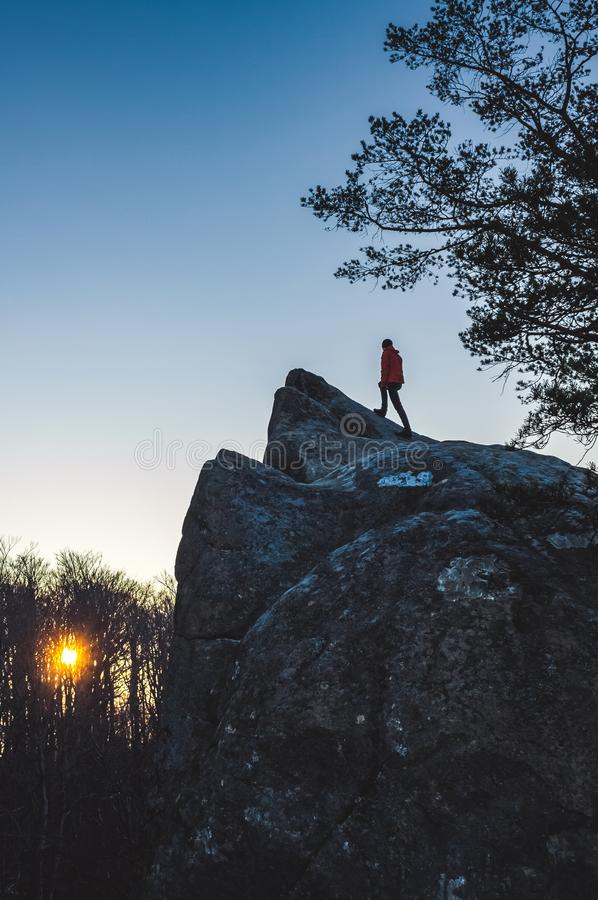 Homem na parte superior da rocha que olha no nascer do sol fotos de stock royalty free