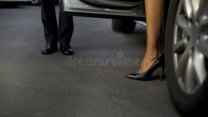 Homem na porta de carro da abertura do terno para o chefe fêmea colocado saltos alto, deveres do trabalho, close-up fotografia de stock royalty free