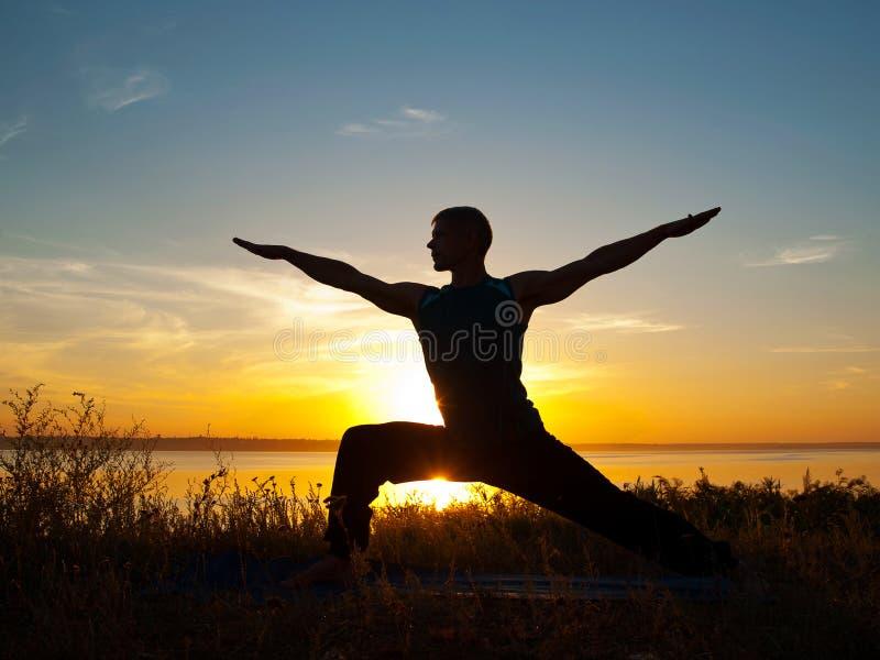 Homem na pose do guerreiro da ioga imagem de stock