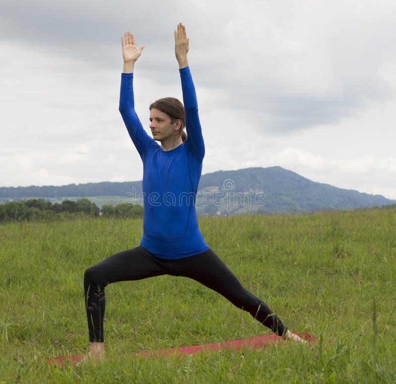 Homem na pose do guerreiro durante a ioga fora na natureza fotos de stock