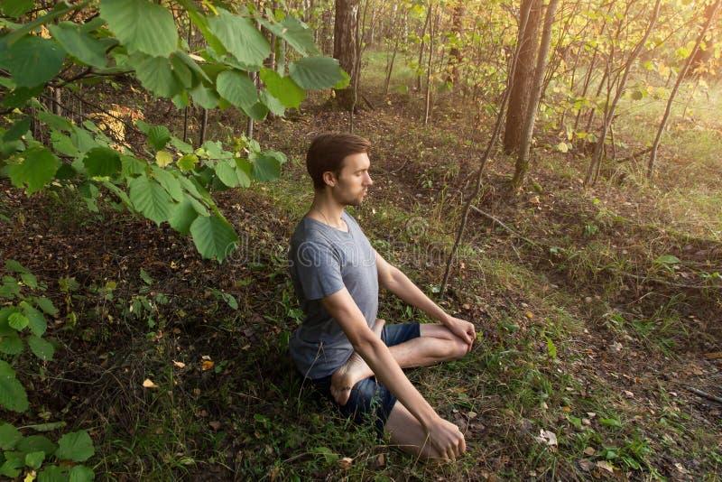 Homem na pose dos lótus que medita fora na natureza da floresta fotos de stock