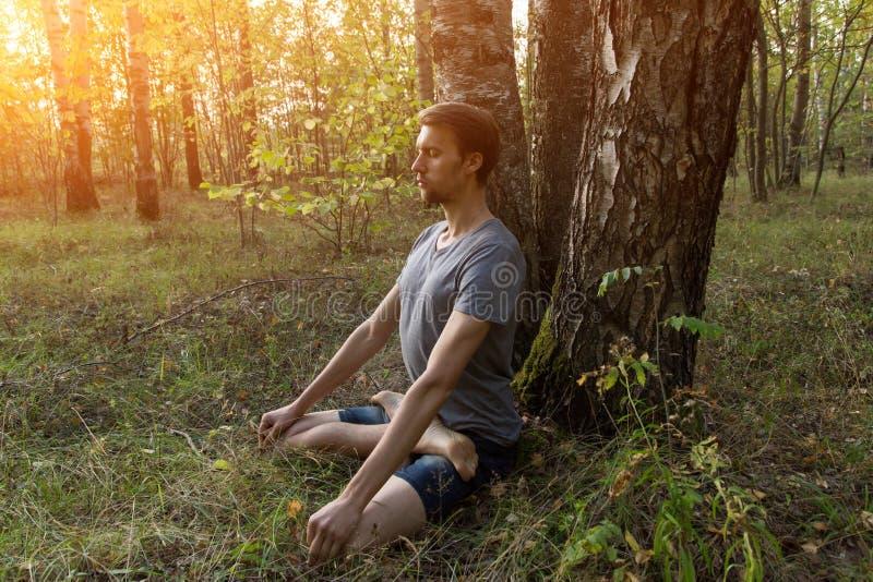 Homem na pose dos lótus que medita fora a natureza na luz solar fotos de stock royalty free