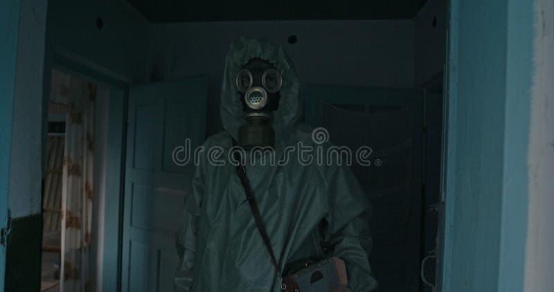 Homem na posição da máscara do terno e de gás do vintage WWII Hazmat na entrada de uma casa O dosímetro na zona de Chernobyl fotografia de stock