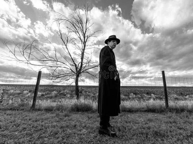 Homem na posição preta da capa de chuva e do chapéu negro na frente da árvore despida preto e branco fotos de stock royalty free