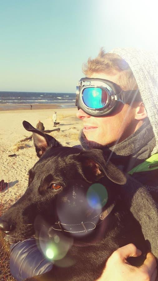 Homem na praia com cão fotografia de stock royalty free