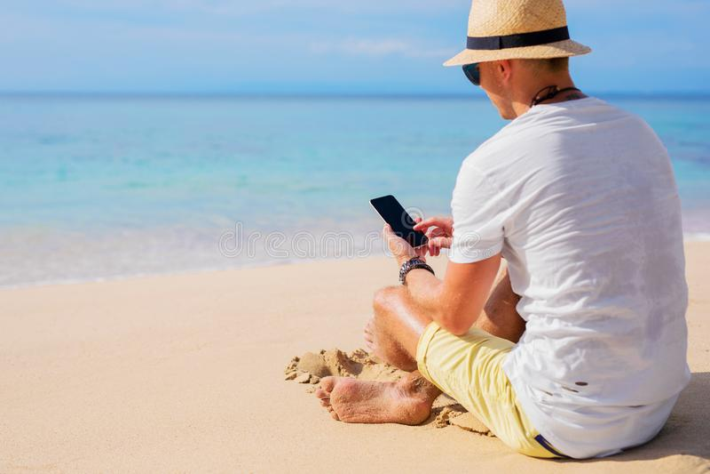Homem na praia com telefone celular fotos de stock royalty free