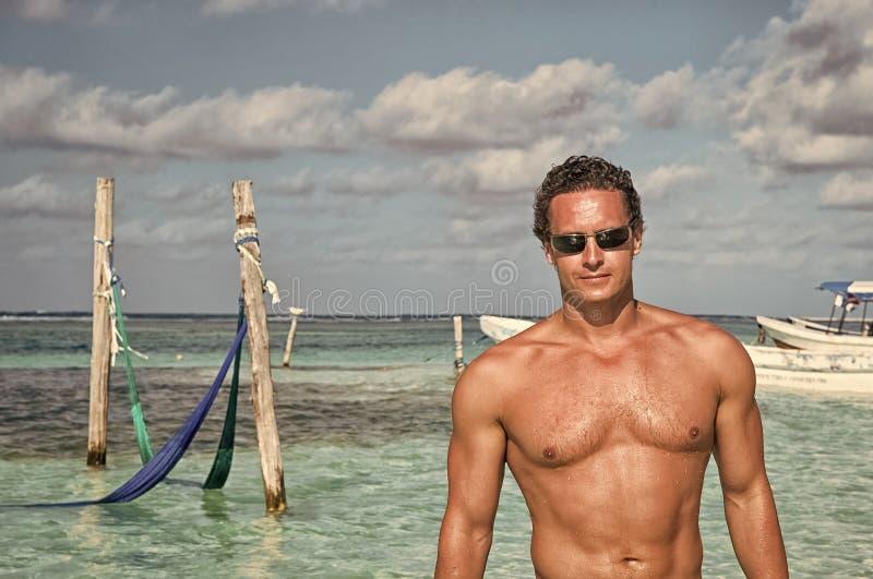 Homem na praia do mar no maya da costela, México O homem 'sexy' com torso muscular aprecia o dia ensolarado na praia das caraíbas imagens de stock royalty free