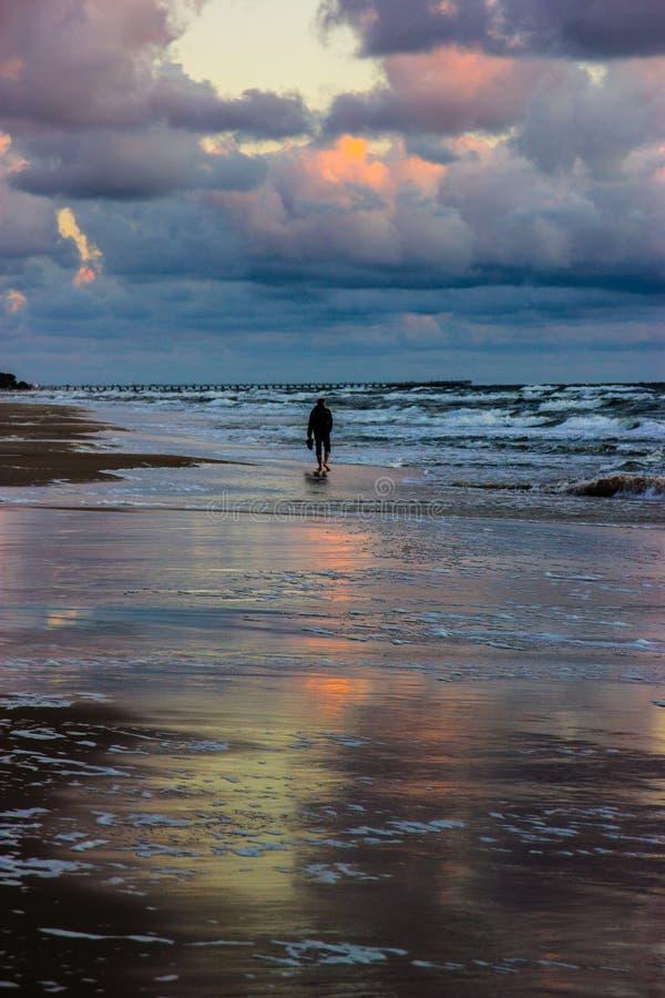 Homem na praia no por do sol sobre o Báltico imagem de stock royalty free