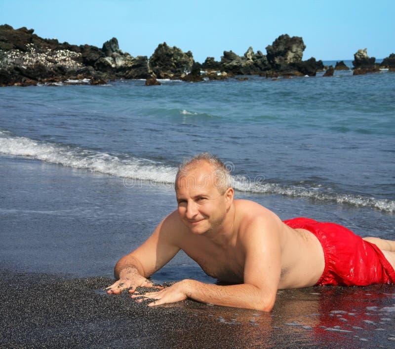 Homem na praia preta da areia fotografia de stock royalty free