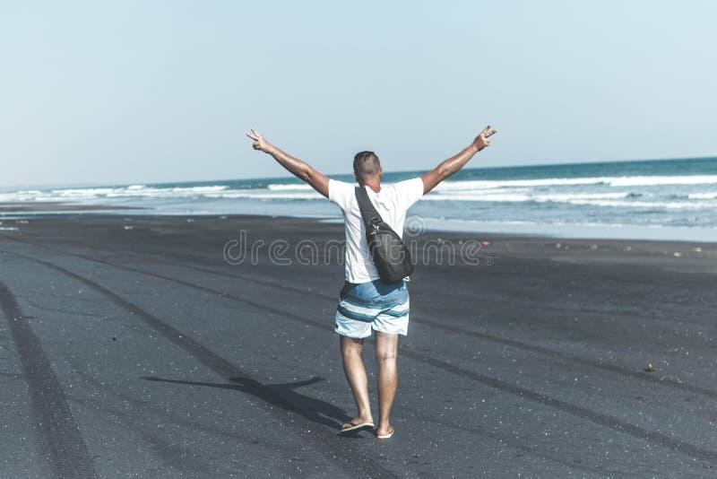 Homem na praia preta da areia Ilha de Bali fotos de stock royalty free