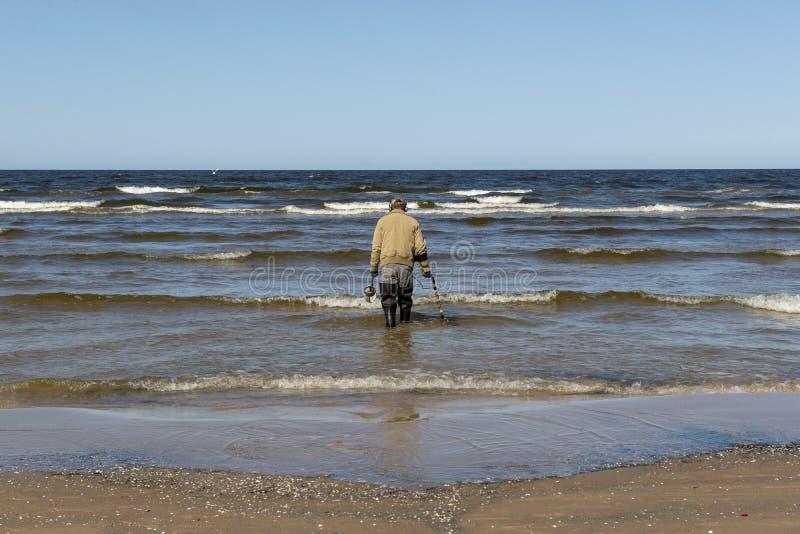 Homem na praia que procura o ouro imagem de stock
