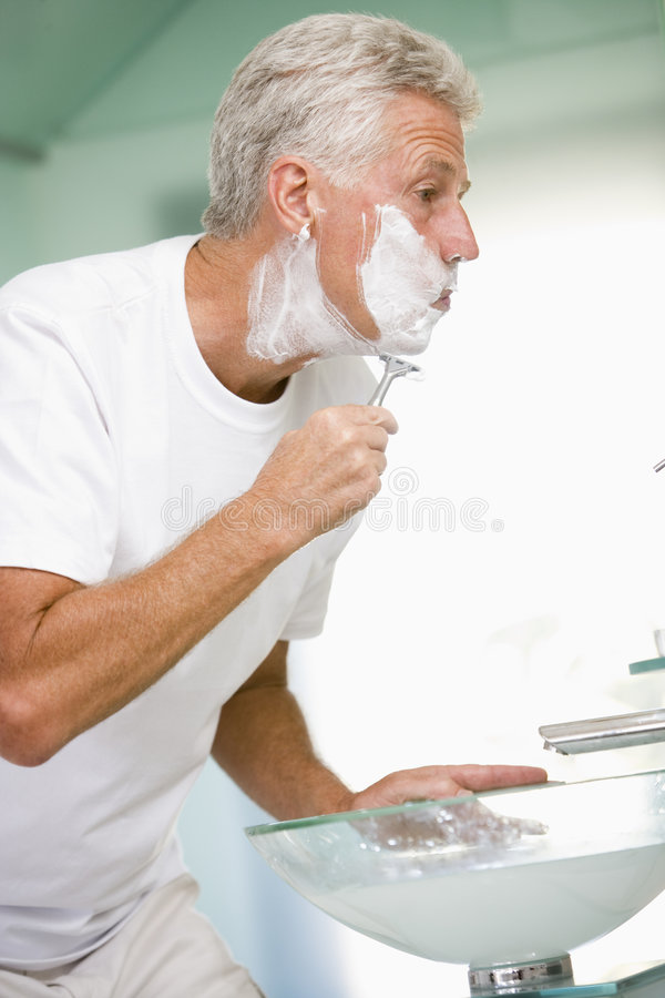Homem na rapagem do banheiro fotografia de stock