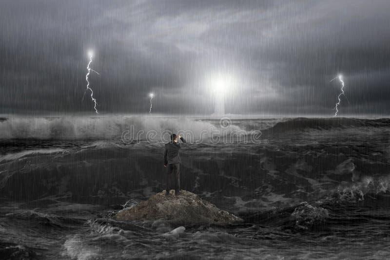 Homem na rocha que olha o farol no oceano com tempestade fotografia de stock