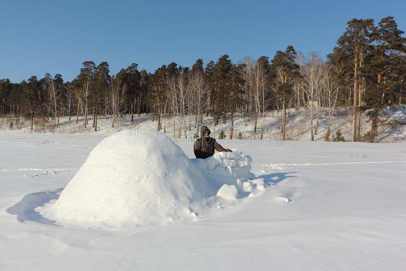 Homem na roupa morna que constrói um iglu em uma clareira nevado no inverno, Sibéria, Rússia foto de stock royalty free