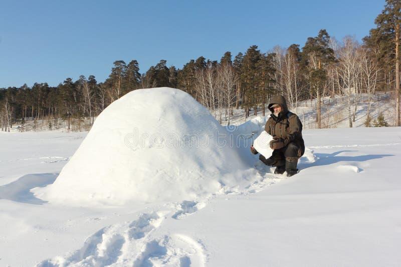 Homem na roupa morna que constrói um iglu em uma clareira nevado no inverno, Sibéria, Rússia fotografia de stock royalty free