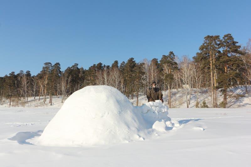 Homem na roupa morna que constrói um iglu em uma clareira nevado no inverno, Sibéria, Rússia fotos de stock royalty free